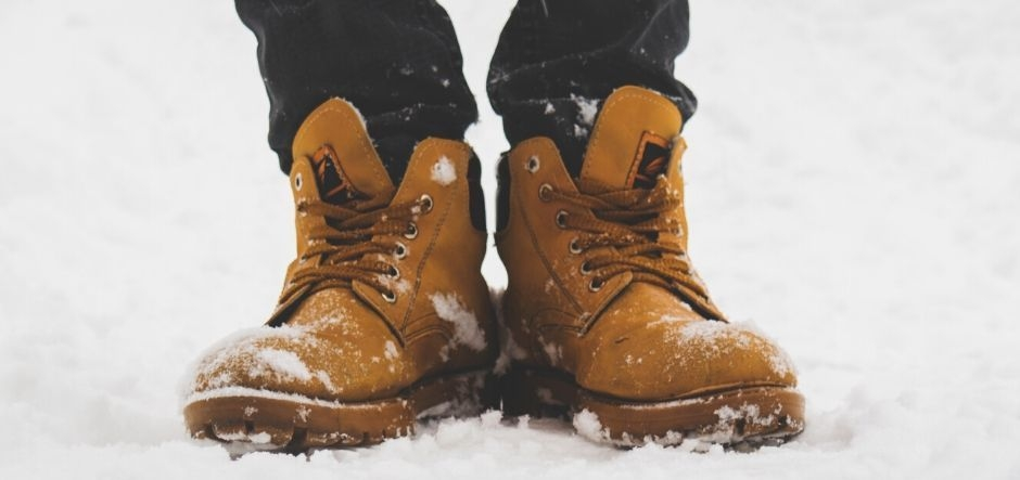 Worker boots standing on top of snow