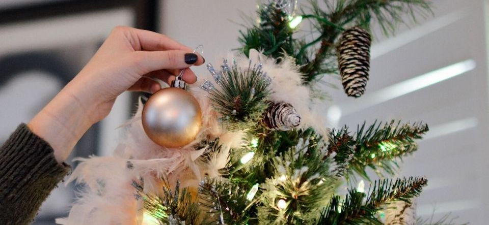 Hand hanging a christmas ornament on a tree