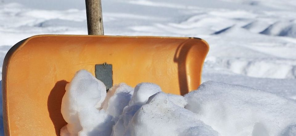 yellow snow shovel pushing a mound of white snow