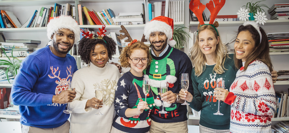 Multi ethnic group of coworkers celebrate New Year in office. They are in office holding champagne glasses, celebrating ugly sweater day.