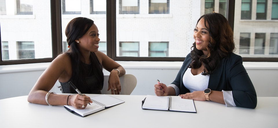 Two women in a conference room smiling