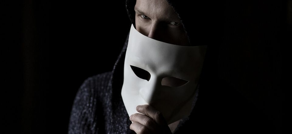 Sinister looking man putting a mask over his face