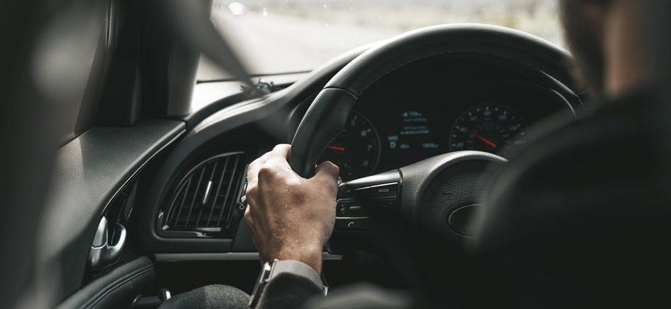 Man driving a car with hands in correct position on steering wheel