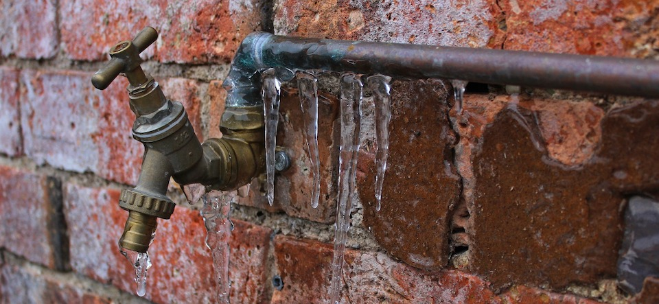 outdoor spigot with icicles on the pipes