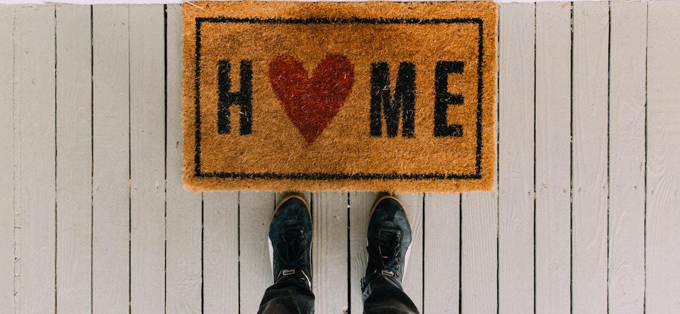 Welcome mat that says Home with a heart in it