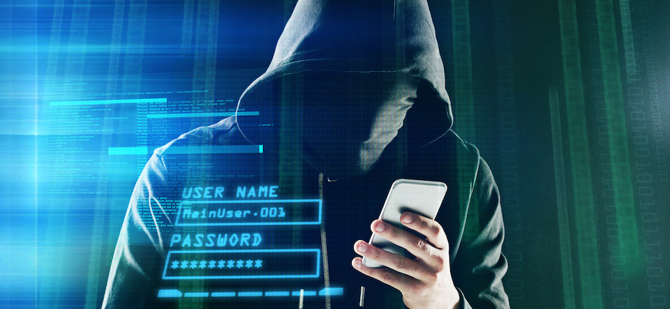 Shot of an unidentifiable computer hacker using a smartphone while standing against a dark background