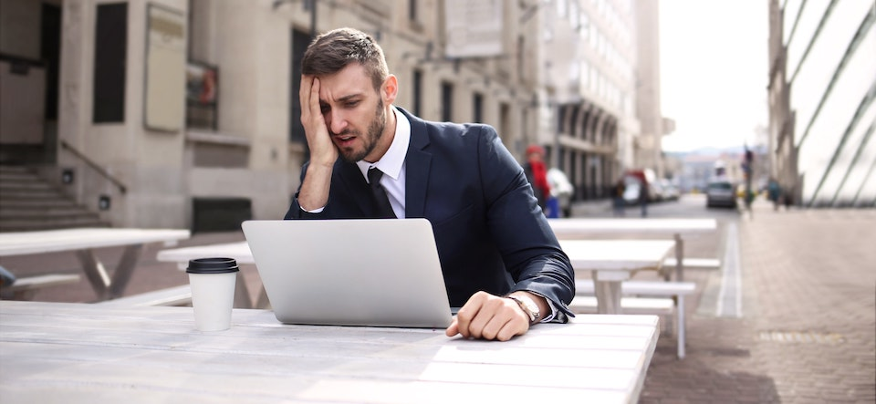 Man in a business suit sitting at a picnic table hand on his face looking at his laptop in confusion