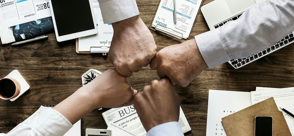 Hands fist-bumping over a corporate table