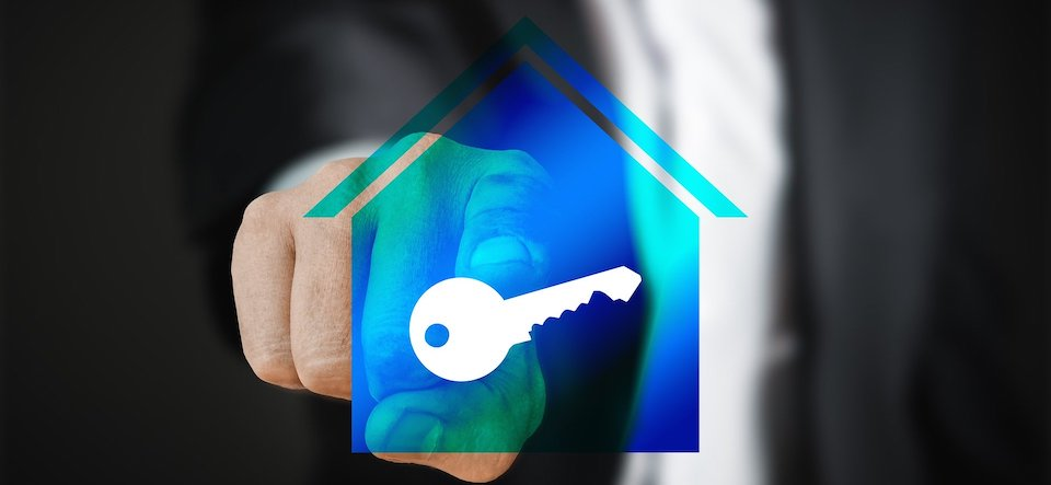 Finger pointing at a key within a translucent image of a house