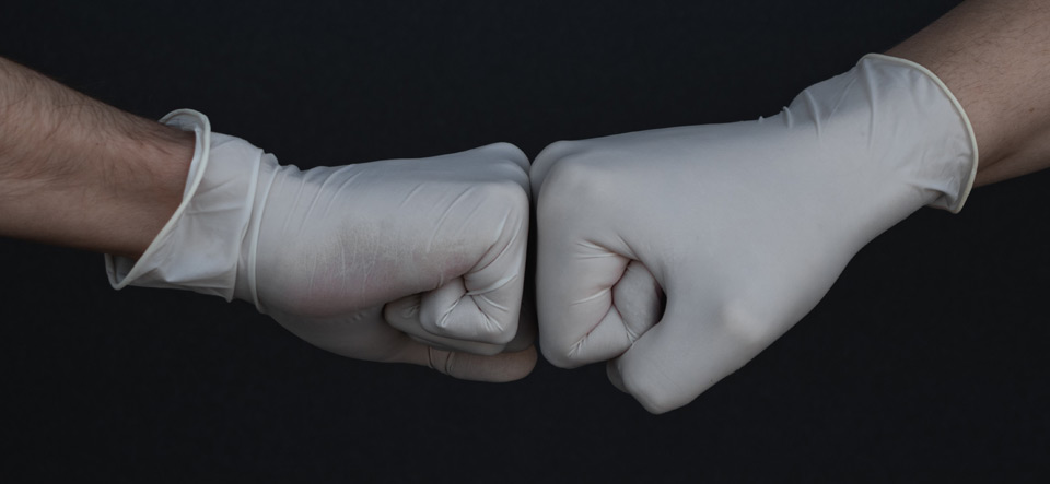 Hands in medical gloves fist bumping