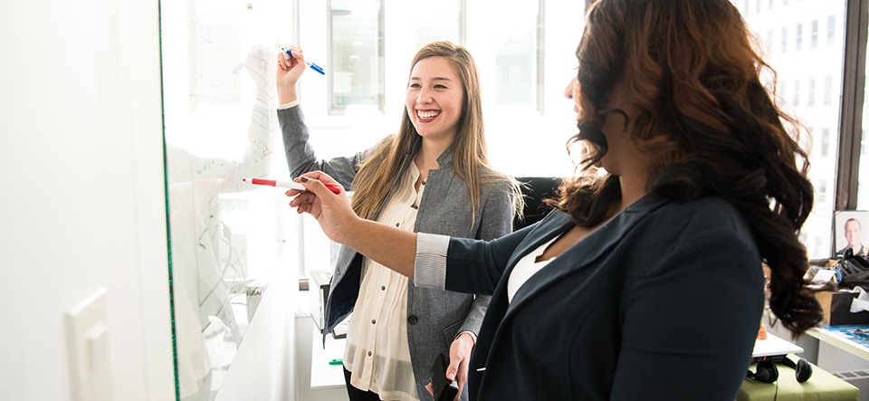 Two business women collaborating at a white board