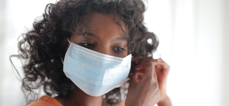 serious black woman putting on a surgical mask