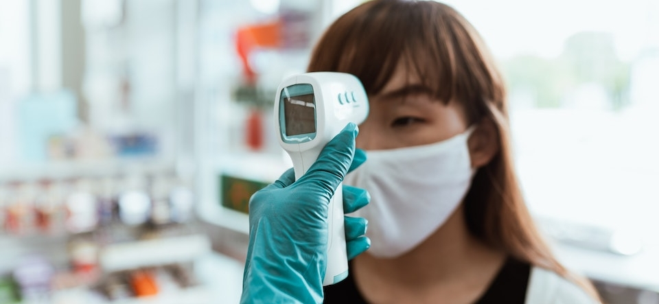 Woman in a mask getting her temperature read