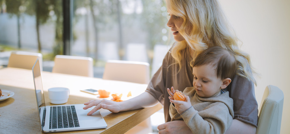 Woman working with her child in her lap