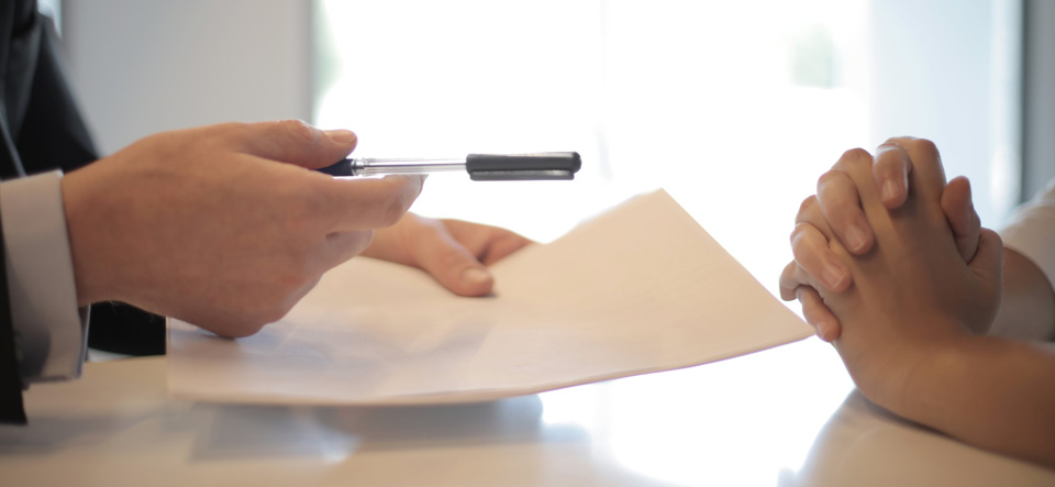 Two people writing and signing an agreement