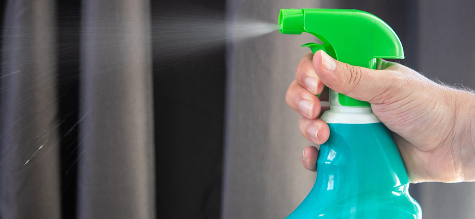 Hand spraying disinfectant from a spray bottle