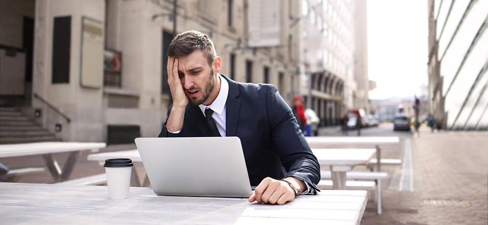 Frustrated business man working at his laptop in a public outdoor space