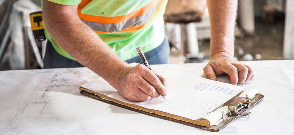 Construction worker filling out a report with pen and paper