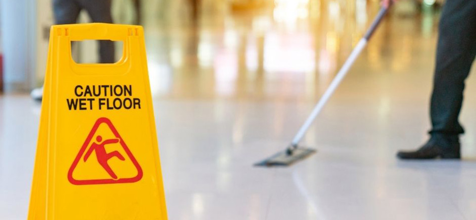 Employee mopping a floor with a warning sign placed