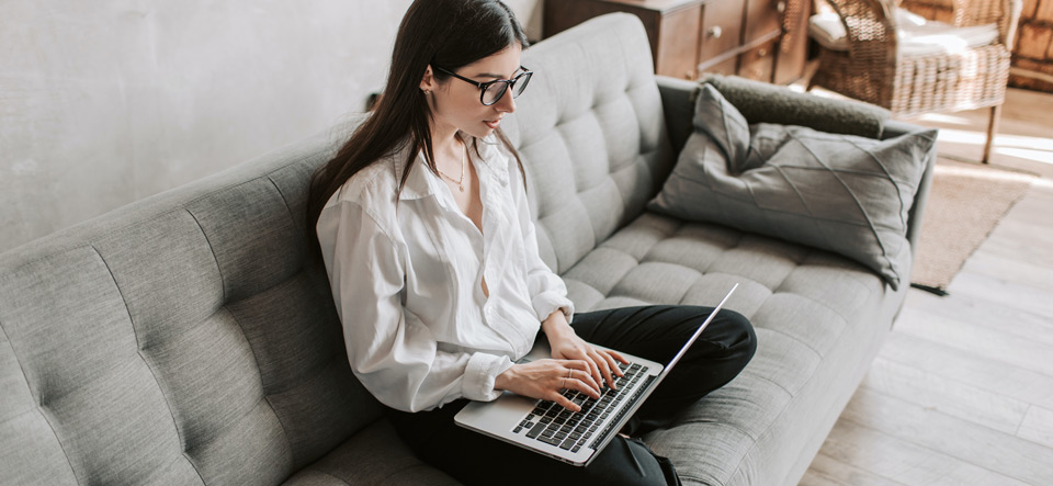 Woman working on her laptop from the comfort of home