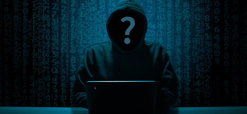 Unknown hacker sitting at computer in a darkened room