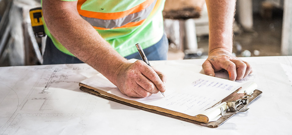 Construction worker filling out paperwork on a job site