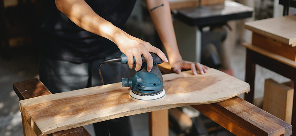 Wood worker sanding a board with a random orbital sander