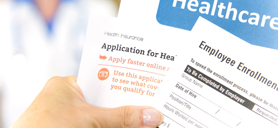 Open enrollment healthcare benefits forms with a medical doctor in the background.  Healthcare remains an important topic around the world!