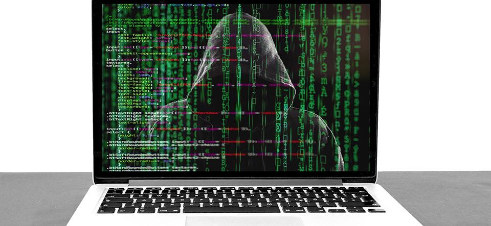 Silhouette of hacker in a hoodie hiding behind Matrix rain computer code