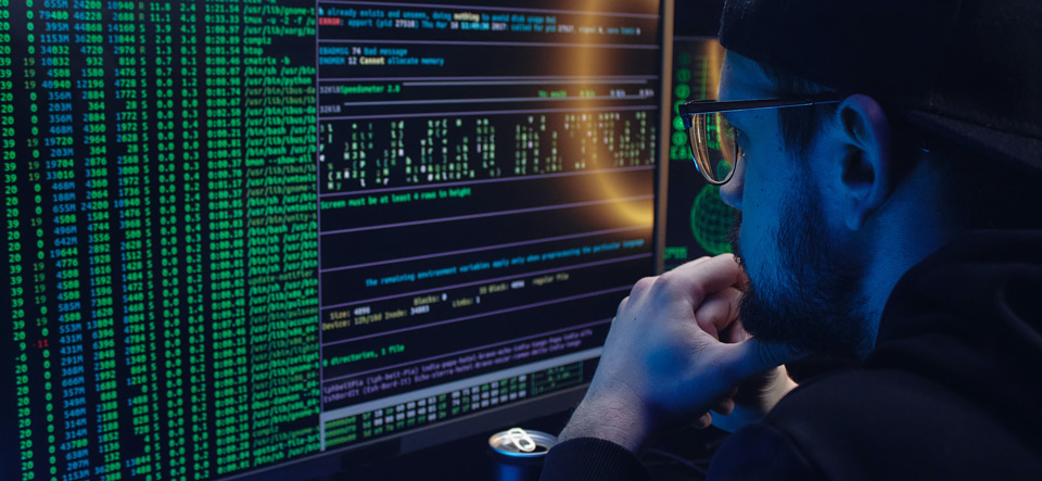 Hacker looking intently at his computer screen