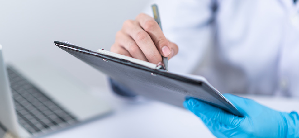 A healthcare worker filling out information on a clipboard