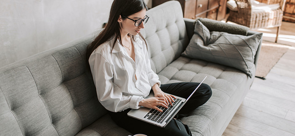 A woman working on her couch at home