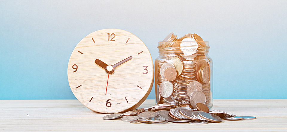 wooden alarm clock and coins on white background
