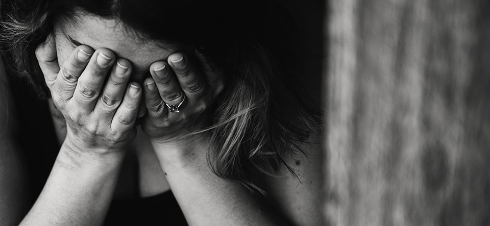 Woman holding her face in her hands because of anxiety